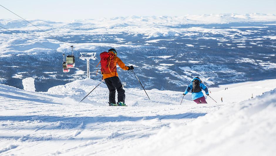 Bild på utförsåkare i en slalombacke med utsikt över fjäll