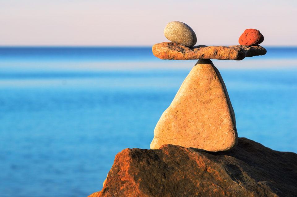Balanserade stenar mot havsbakgrund