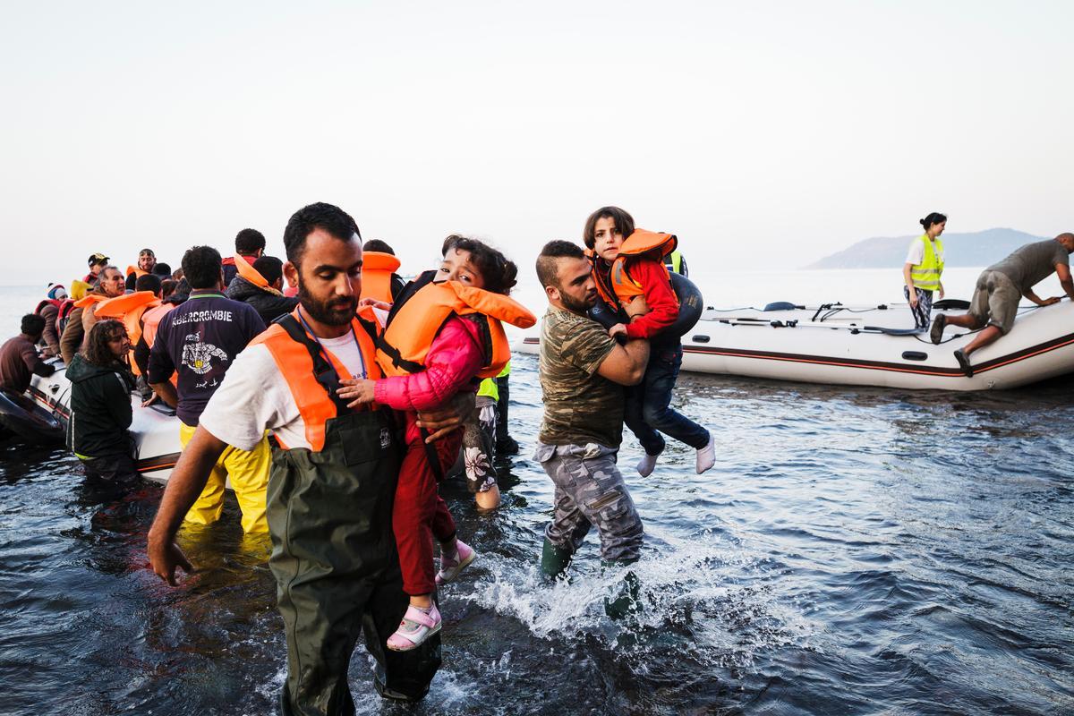 Barn som bärs iland från flyktingbåt.