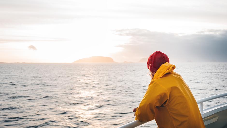 Person vid reling på båt tittar ut över havet